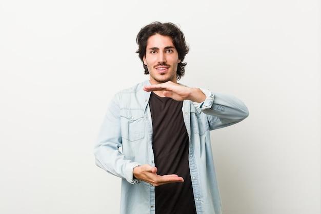 Junger gutaussehender mann gegen einen weißen hintergrund, der etwas mit beiden händen, produktdarstellung hält.