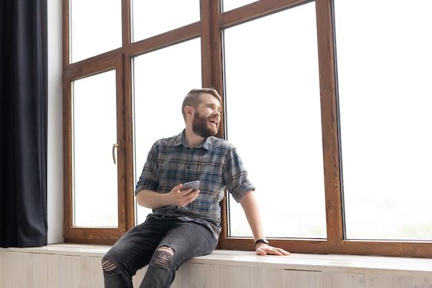 Junger gutaussehender mann-hipster, der auf der fensterbank nahe einem großen fenster mit einem smartphone in seinem sitzt