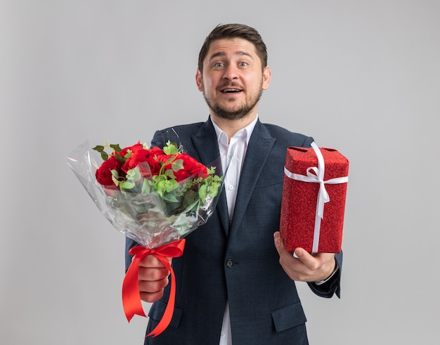 Junger gutaussehender mann im anzug mit rosenstrauß und einem geschenk zum valentinstag glücklich und aufgeregt über weißer wand stehend