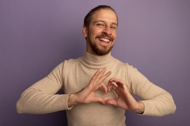 Junger gutaussehender mann im beigen rollkragenpullover, der nach vorne lächelt und fröhlich herzgeste mit den fingern macht, die über fliederwand stehen