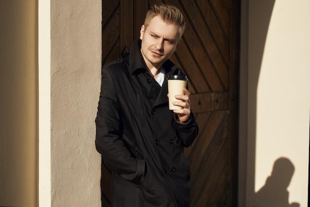 Junger gutaussehender mann im dunklen mantel mit tasse kaffee