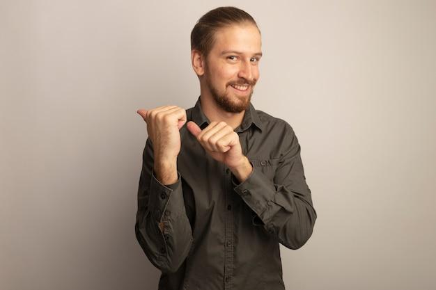 Junger gutaussehender mann im grauen hemd, das die vordere lächelnde selbstbewusste spitze mit zeigefingern zur seite betrachtet, die über weißer wand steht