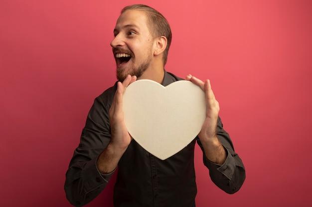 Junger gutaussehender mann im grauen hemd, das pappherz hält, das beiseite schaut, das fröhlich lächelt