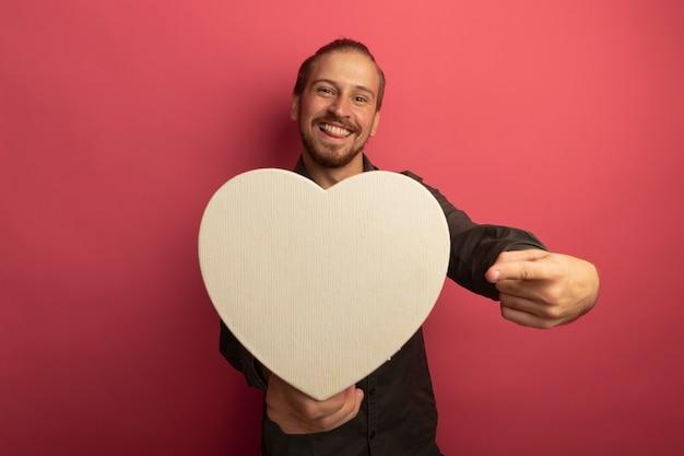 Junger gutaussehender mann im grauen hemd, das pappherz hält, das mit zeigefinger darauf zeigt und mit glücklichem gesicht lächelt