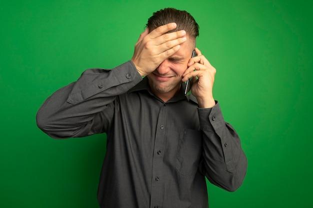 Junger gutaussehender mann im grauen hemd, das verwirrt mit der hand auf seinem kopf schaut, während auf handy spricht