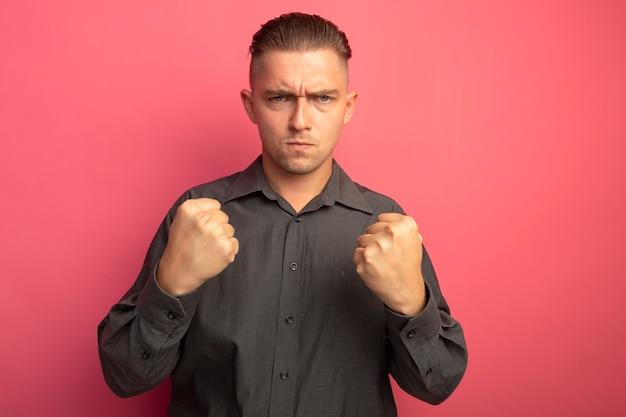 Junger gutaussehender mann im grauen hemd, das vorne mit wütendem stirnrunzeln die geballten fäuste betrachtet, die über rosa wand stehen