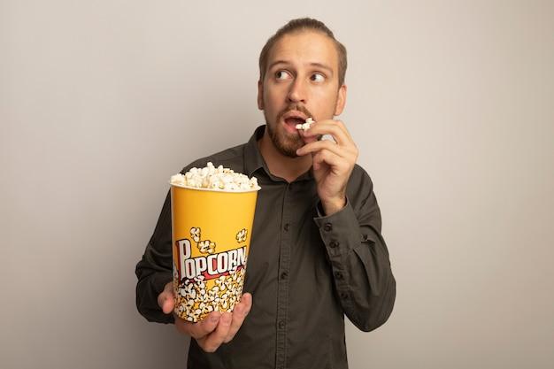 Junger gutaussehender mann im grauen hemd, der eimer mit popcorn hält und das essen betrachtet, das verwirrt über weißer wand steht