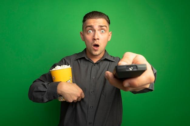Junger gutaussehender mann im grauen hemd, der eimer mit popcorn unter verwendung der fernsehfernbedienung hält, die vorne erstaunt über grünes wandstand steht