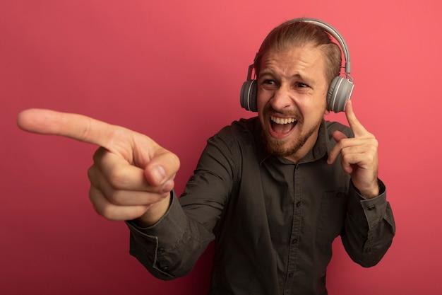 Junger gutaussehender mann im grauen hemd mit kopfhörern auf seinem kopf, der beiseite schreit und gereizt ist und mit indexfigner auf etwas zeigt