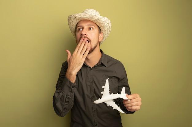 Junger gutaussehender mann im grauen hemd und im sommerhut, der spielzeugflugzeug hält, das erstaunte, bedeckten mund mit hand bedeckt