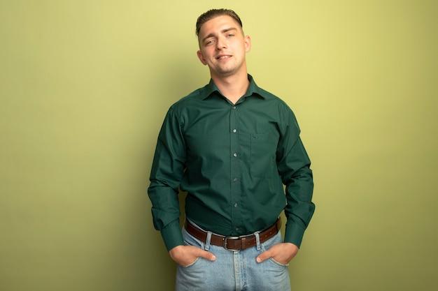 Junger gutaussehender mann im grünen hemd, das zuversichtlich hand in taschen hält lächelnd