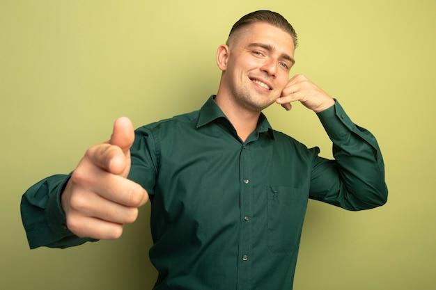 Junger gutaussehender mann im grünen hemd lächelt mit glücklichem gesicht, das daumen hoch zeigt, die mich geste nennen