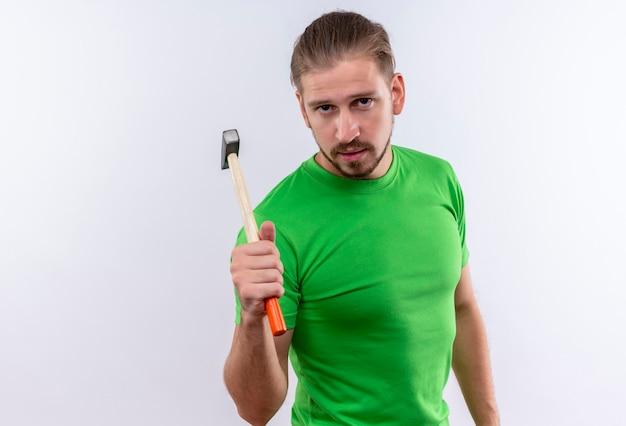 Junger gutaussehender mann im grünen t-shirt, der hammer betrachtet kamera mit ernstem gesicht, das über weißem hintergrund steht