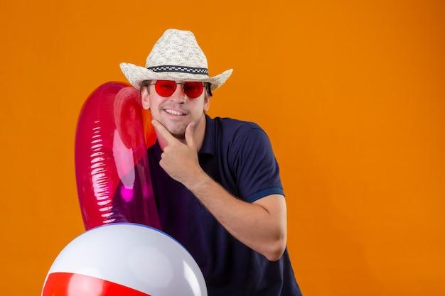 Junger gutaussehender mann im sommerhut, der rote sonnenbrille hält, die aufblasbaren ball und ring hält, die kamera mit dem selbstbewussten lächeln des selbstbewussten lächelns über orange hintergrund betrachten