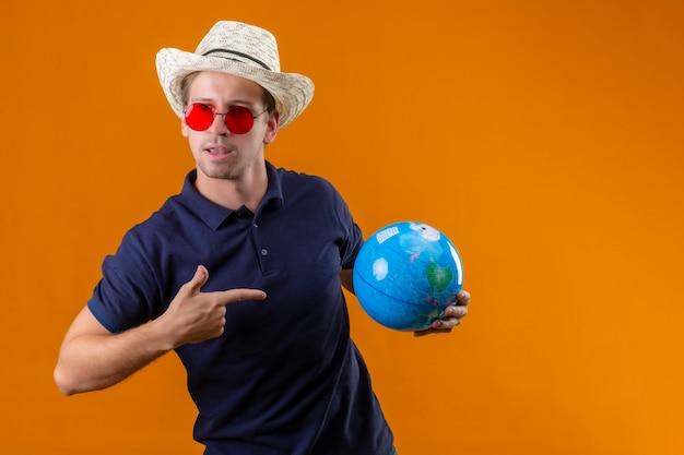 Junger gutaussehender mann im sommerhut, der rote sonnenbrille hält, die globus zeigt finger mit ihm mit sicherem ausdruck auf gesicht steht über orange hintergrund