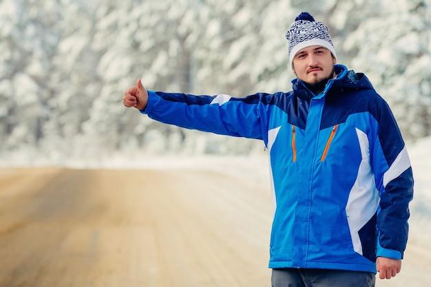 Junger gutaussehender mann in blauer jacke im winter, stand auf der autobahn und trampte