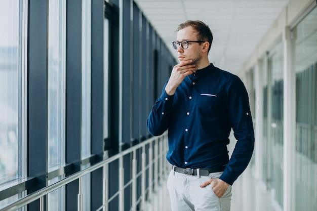 Junger gutaussehender mann in der büromitte