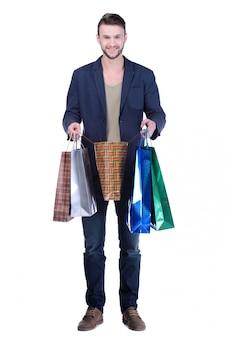 Junger gutaussehender mann in der klage mit einkaufstaschen.