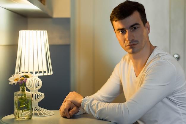 Junger gutaussehender mann in der weißen abnutzung, die im café aufwirft