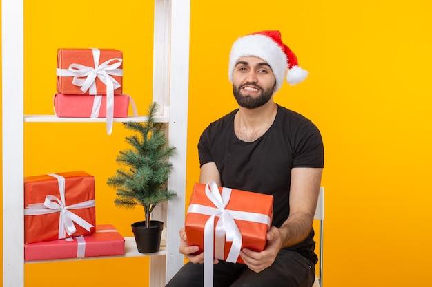 Junger gutaussehender mann in einem weihnachtsmann-hut hält glückwunschgeschenke neben einem weihnachtsbaum. konzept der feiertage von weihnachten und neujahr.