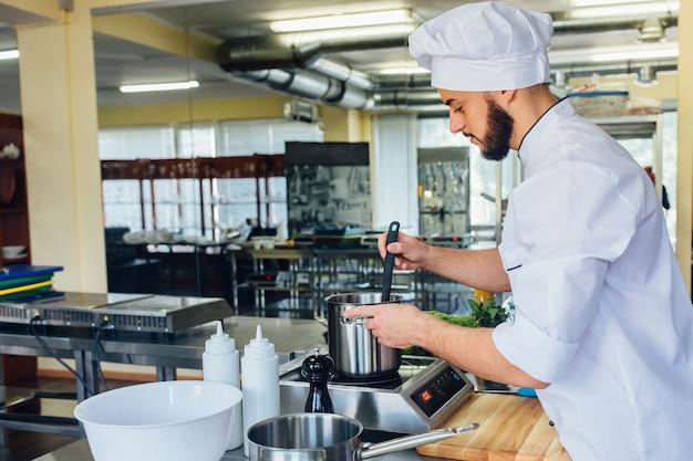 Junger gutaussehender mann in einem weißen spezialgewand, der pasta zubereitet, kocht wasser für italienische spaghetti.