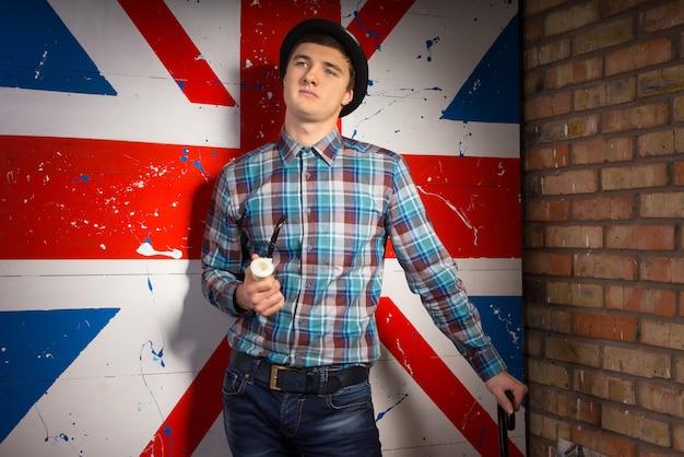 Junger gutaussehender mann in kariertem hemd und jeans-outfit mit pfeife und rohrstock posiert vor riesigem uk-flaggendruck