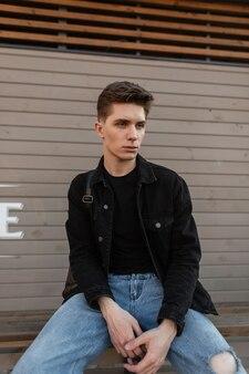 Junger gutaussehender mann in modischer jeansjacke in blauer stylischer jeans mit rucksack