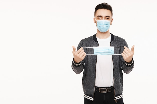 Junger gutaussehender mann in schutzmaske hält eine andere medizinische maske in händen