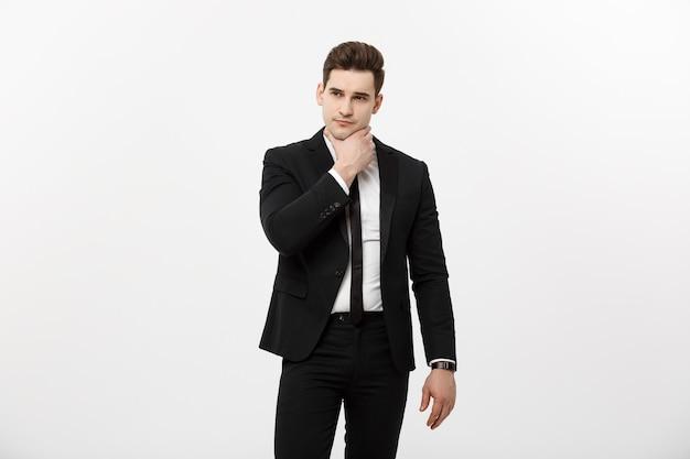 Junger gutaussehender mann in schwarzem anzug und brille, der kopienraum betrachtet oder träumt, isoliert über...