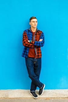 Junger gutaussehender mann in stilvollen kleidern und turnschuhen wirft nahe der blauen wand auf