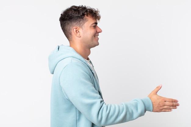 Junger gutaussehender mann lächelt, begrüßt sie und bietet einen handschlag an, um ein erfolgreiches geschäft abzuschließen, kooperationskonzept