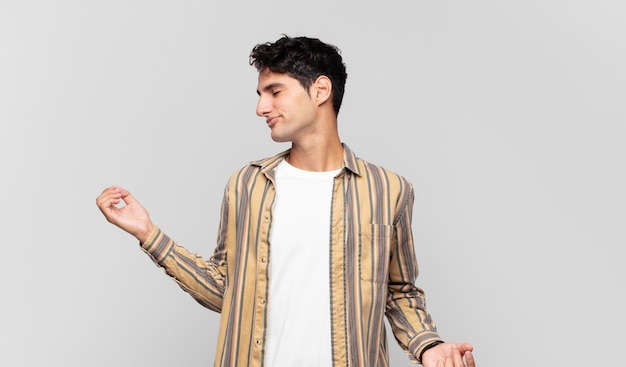 Junger gutaussehender mann lächelt, fühlt sich sorglos, entspannt und glücklich, tanzt und hört musik, hat spaß auf einer party