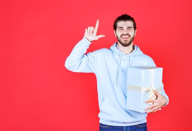 Junger gutaussehender mann lächelt und hält seinen finger hoch