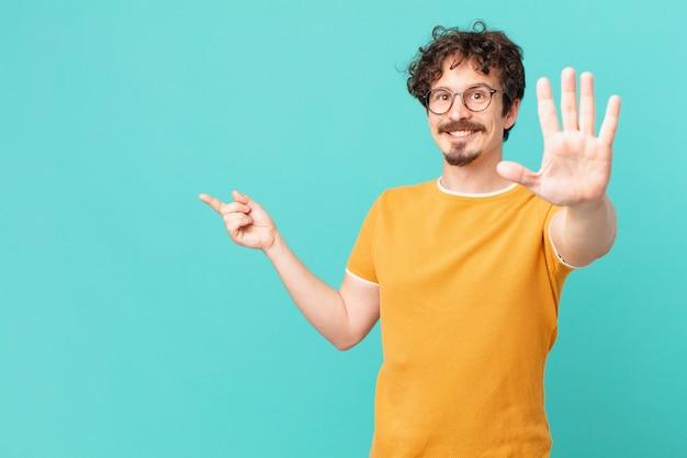 Junger gutaussehender mann lächelt und sieht freundlich aus und zeigt nummer fünf showing