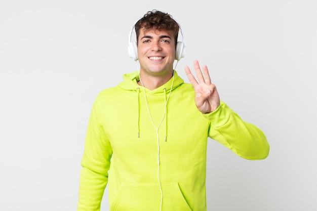 Junger gutaussehender mann lächelt und sieht freundlich aus, zeigt nummer drei und kopfhörer