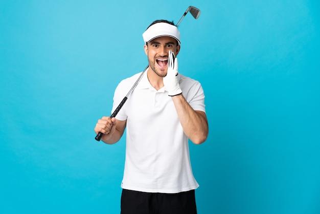 Junger gutaussehender mann lokalisiert auf blauem hintergrund, der golf spielt und mit mund weit offen schreit