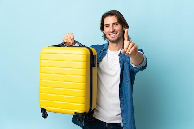 Junger gutaussehender mann lokalisiert auf blauem hintergrund im urlaub mit reisekoffer und zählen eines