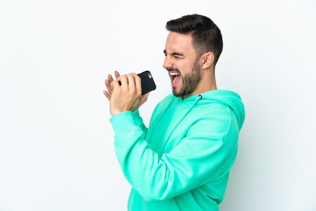 Junger gutaussehender mann lokalisiert auf weißer wand unter verwendung des mobiltelefons und des singens