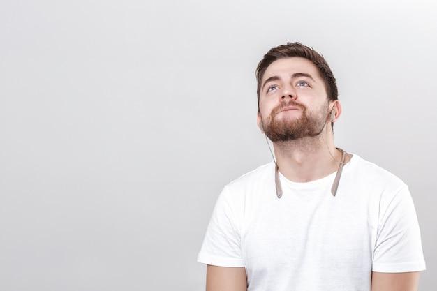 Junger gutaussehender mann mit bart im t-shirt, der musik über kopfhörer hört