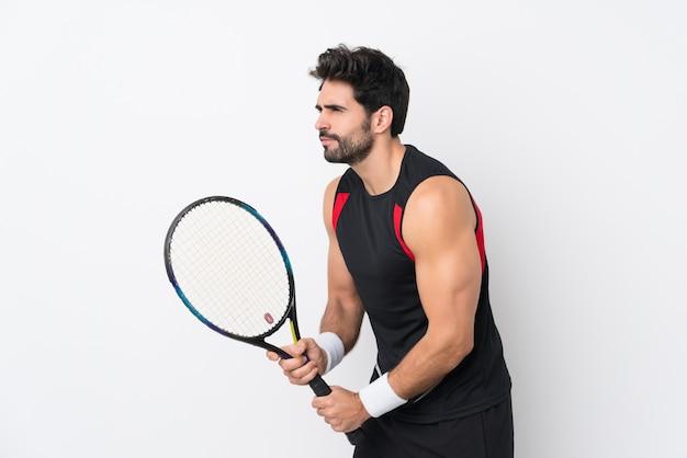 Junger gutaussehender mann mit bart über der lokalisierten weißen wand, die tennis spielt