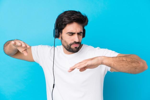 Junger gutaussehender mann mit bart über hörender musik und tanzen der lokalisierten blauen wand