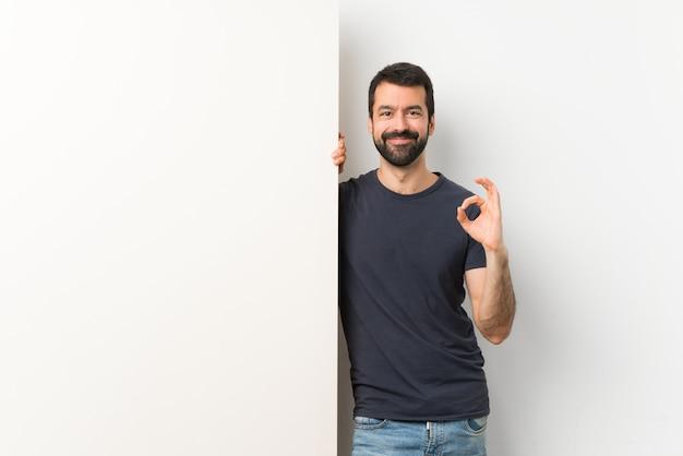 Junger gutaussehender mann mit dem bart, der ein darstellendes okayzeichen mit den fingern hält