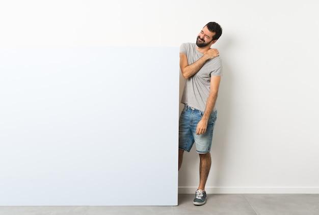 Junger gutaussehender mann mit dem bart, der ein großes blaues leeres plakat leidet unter den schmerz in der schulter für das haben einer bemühung hält