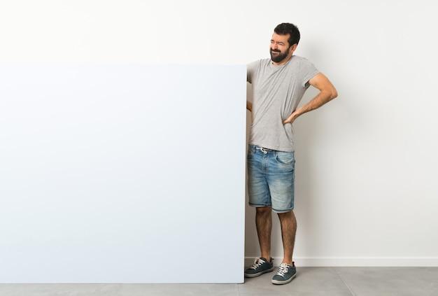 Junger gutaussehender mann mit dem bart, der ein großes blaues leeres plakat leidet unter rückenschmerzen hält, weil er sich bemüht hat