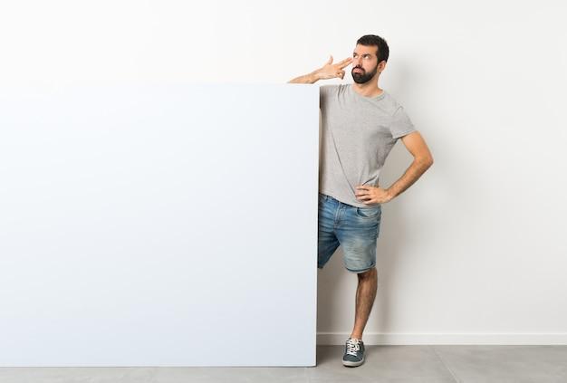 Junger gutaussehender mann mit dem bart, der ein großes blaues leeres plakat mit den problemen machen selbstmordgeste hält