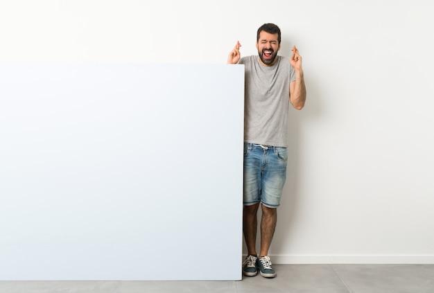Junger gutaussehender mann mit dem bart, der ein großes blaues leeres plakat mit der fingerüberfahrt hält