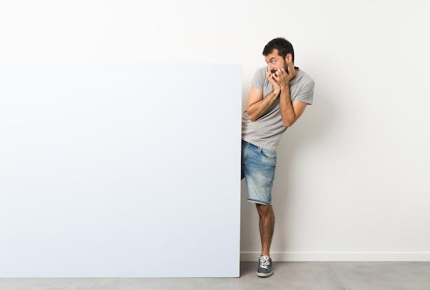 Junger gutaussehender mann mit dem bart, der ein großes blaues leeres plakat nervös und erschrocken hält, hände zum mund setzend