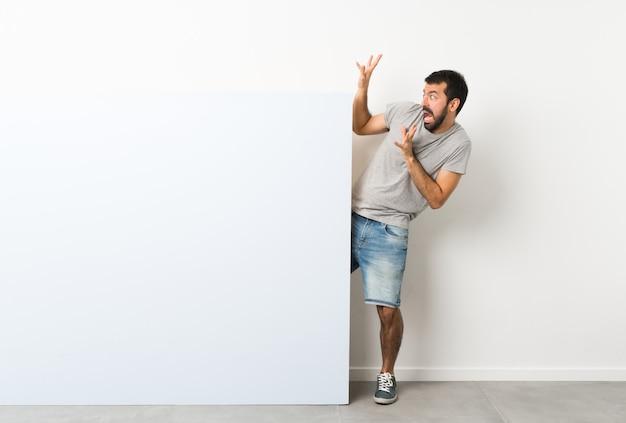 Junger gutaussehender mann mit dem bart, der ein großes blaues leeres plakat nervös und erschrocken hält