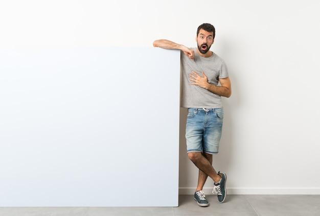 Junger gutaussehender mann mit dem bart, der ein großes blaues leeres plakat überrascht und beim schauen entsetzt hält