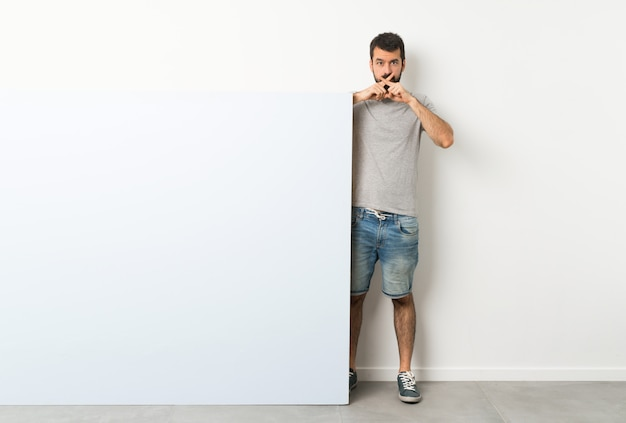 Junger gutaussehender mann mit dem bart, der ein großes blaues leeres plakat zeigt ein zeichen der ruhegeste hält